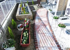 自然石の素材を使った花壇。勝手口へと通じるアプローチ通路です。